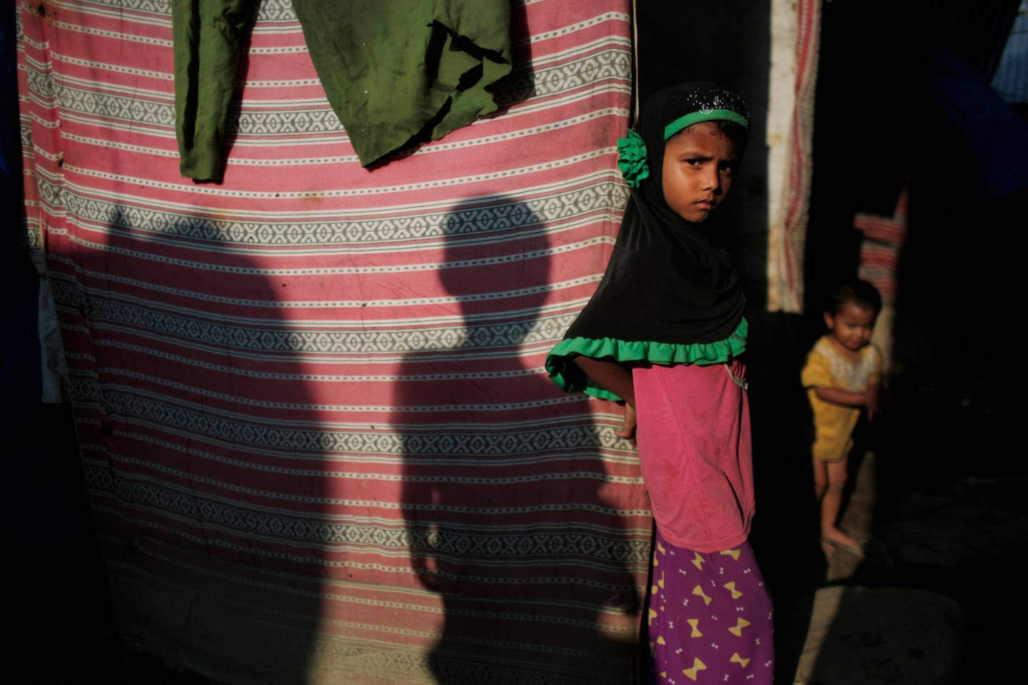In this Sunday, Sept. 10, 2017, photo, a young Rohingya stands outside her temporary shelter at a camp in Kathmandu, Nepal. Recent violence in Myanmar has driven hundreds of thousands of Rohingya Muslims to seek refuge across the border in Bangladesh. Only about 250 Rohingya live in Nepal since anti-Muslim riots erupted in Myanmar in 2012, according to the U.N. refugee agency, which offers them education and medical support. The refugees live in a ramshackle camp carved out on a slope on the outskirts of the capital, Kathmandu. Their huts of tin, bamboo and plastic sheets are connected by narrow stone steps. (AP Photo/Niranjan Shrestha)