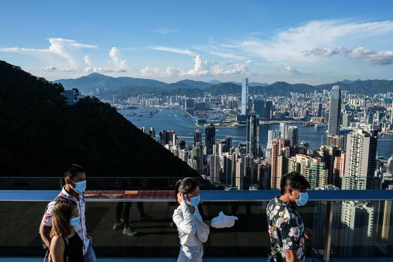 (FILES) In this file photo taken on July 28, 2020, visitors walk along a viewing platform on Victoria Peak in Hong Kong. Hong Kong and Singapore announced on April 26, 2021 plans to resurrect their scrapped coronavirus travel bubble with dedicated flights between the two cities starting on May 26. / AFP / Afp / ANTHONY WALLACE