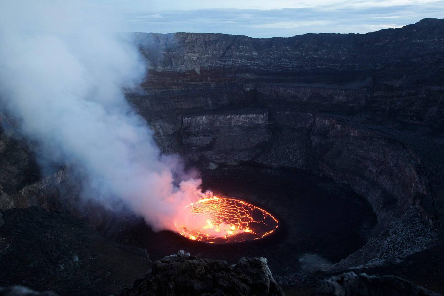 In this March 31, 2010 photo, smoke rises off of churning magma in the lava lake of Mount Nyiragongo, one of Africa's most active volcanos, outside Goma, Congo. Mount Nyiragongo is the ultimate symbol of death in Goma, the lakeside city it shadows and has overrun several times. Yet it's also a symbol of rebirth and resilience for a nation slowly emerging from war. In March, park rangers cleared Rwandan militias from its slopes and reopened the summit for the first time in a year and a half. (AP Photo/Rebecca Blackwell)