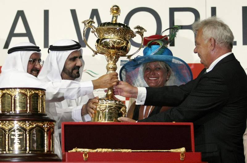 Emirati Finance Minister Sheikh Hamdan bin Rashed al-Maktoum (L) and Dubai ruler Sheikh Mohammed bin Rashed al-Maktoum (2nd-L) give the trophy to Brazilian Stefan Friborg (R) and his wife Dalva de Oliveira, owners of Gloria De Campeao which won the Dubai World Cup, at the Meydan race track in the Gulf emirate on March 27, 2010. French runner Gloria De Campeao won the world's richest race, the 10-million-dollar Dubai World Cup. AFP PHOTO/MARWAN NAAAMANI (Photo by MARWAN NAAMANI / AFP)