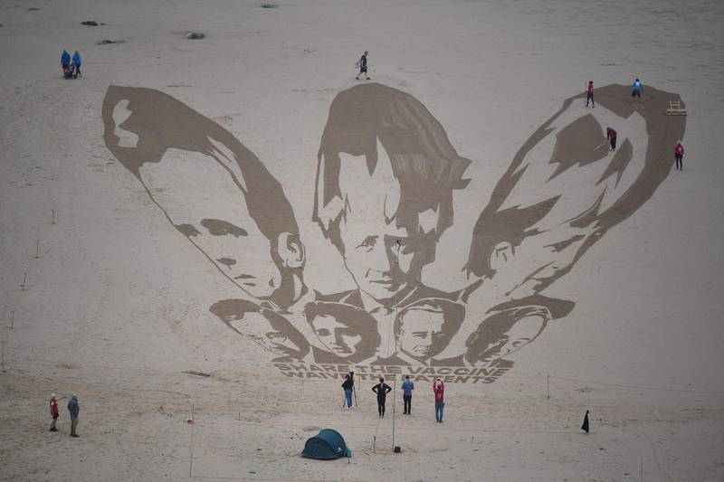 Activists put the finishing touches to a sand drawing of the G7 leaders and calling on them to 'share the vaccine and waive the patents' on Watergate Bay beach near Newquay, Cornwall on June 10, 2021, ahead of the three-day G7 summit being held from 11-13 June.  G7 leaders from Canada, France, Germany, Italy, Japan, the UK and the United States meet this weekend for the first time in nearly two years, for the three-day talks in Carbis Bay, Cornwall. -   / AFP / Ben STANSALL