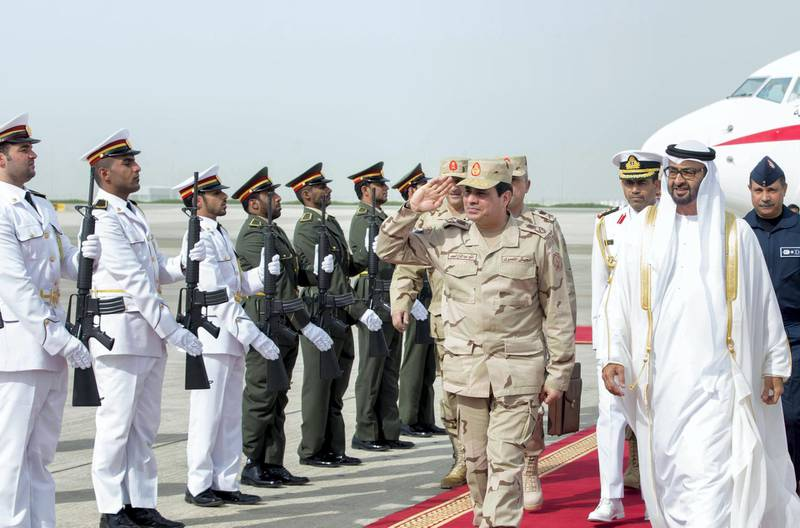 """A picture made available by the United Arab Emirates' official news agency WAM shows Egyptian Defense Minister and Military Chief General Abdel Fattah al-Sisi (C) saluting as he is welcomed by Sheikh Mohamed bin Zayed Al Nahyan Crown Prince of Abu Dhabi (R) upon his arrival in Abu Dhabi on March 11, 2014.  AFP PHOTO/WAM/HO == RESTRICTED TO EDITORIAL USE - MANDATORY CREDIT """"AFP PHOTO / HO / WAM"""" == NO MARKETING NO ADVERTISING CAMPAIGNS - DISTRIBUTED AS A SERVICE TO CLIENTS === (Photo by HO / WAM / AFP)"""