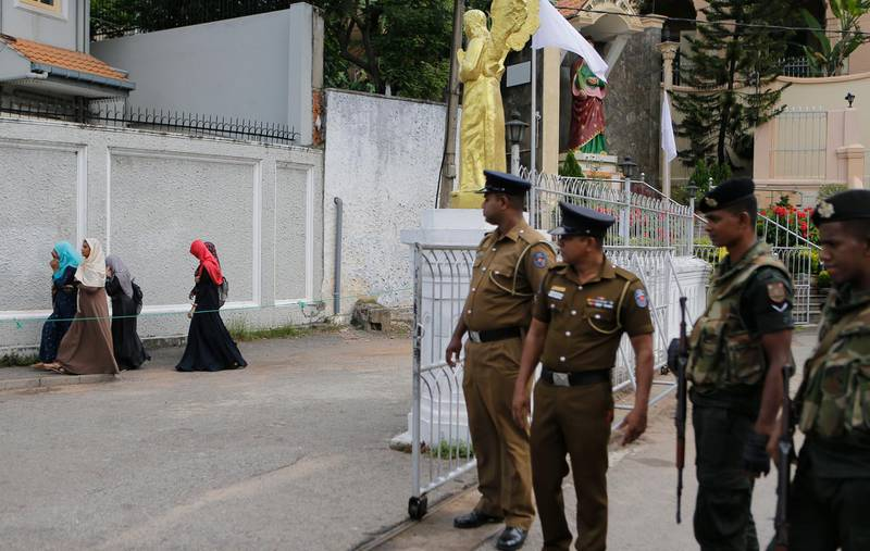 In this Sunday, May 12, 2019, photo, Sri Lankan soldiers watch as a group of Muslim students walk past a closed catholic convent in Colombo, Sri Lanka. Catholic officials and parents in Sri Lanka are hopeful that church-run schools will begin to reopen soon for the first time since April's devastating Easter Sunday attacks on churches and hotels. (AP Photo/Eranga Jayawardena)