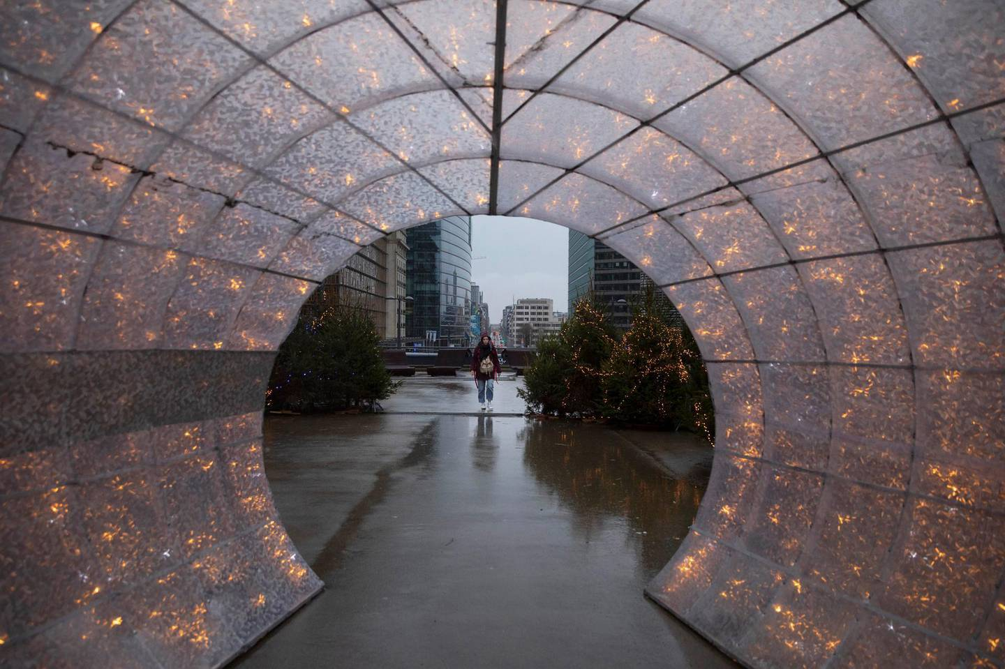 A woman walks amongst Christmas decorations outside of EU headquarters in Brussels, Wednesday, Dec. 23, 2020. France insisted on Wednesday that European Union negotiators should not yield to any time pressure imposed by the Jan. 1 economic cutoff date in the talks with Britain on a trade agreement in the wake of the Brexit divorce, arguing no deal would be better than a bad one. (AP Photo/Virginia Mayo)