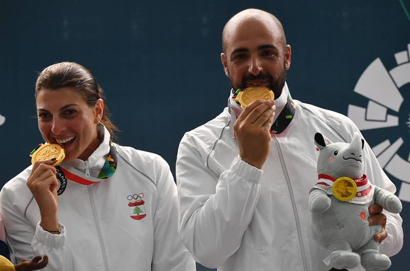 Gold medallists Lebanon's Ray Bassil (L) and Alain Moussa (R) pose for photographers during the victory ceremony for the trap mixed team shooting event at the 2018 Asian Games in Palembang on August 21, 2018. (Photo by ADEK BERRY / AFP)