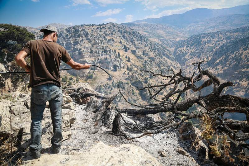 A volunteer works to extinguish a fire in Jird Harar, in Lebanon's Akkar region on Aug. 30, 2020