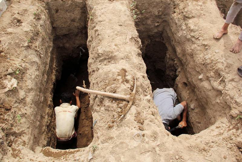 FILE PHOTO: People dig graves at a cemetery where victims of the coronavirus disease (COVID-19) are buried in Taiz, Yemen June 23, 2020. Picture taken June 23, 2020. REUTERS/Anees Mahyoub/File Photo
