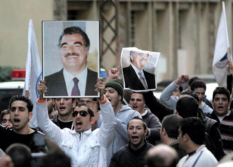 Supporters of former Lebanese prime minister Rafiq Hariri waves his pictures following Hariri's death outside his house in Beirut 14 February 2005. Hariri was killed in a huge explosion in central Beirut.         AFP PHOTO/JOSEPH BARRAK (Photo by JOSEPH BARRAK / AFP)