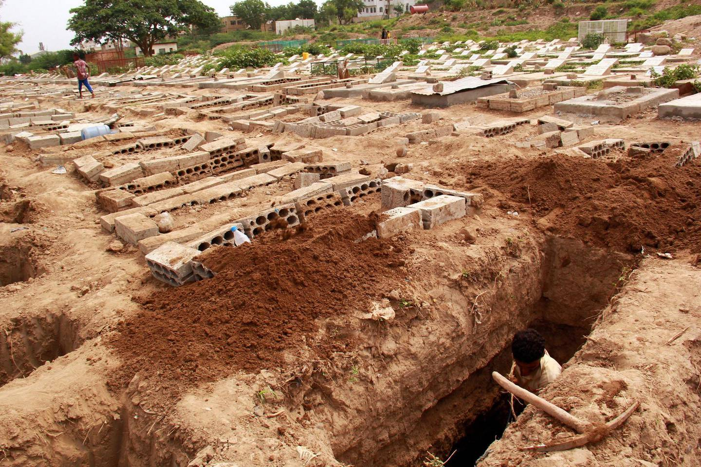 FILE PHOTO: A man digs a grave at a cemetery where victims of the coronavirus disease (COVID-19) are buried in Taiz, Yemen June 23, 2020. Picture taken June 23, 2020. REUTERS/Anees Mahyoub/File Photo