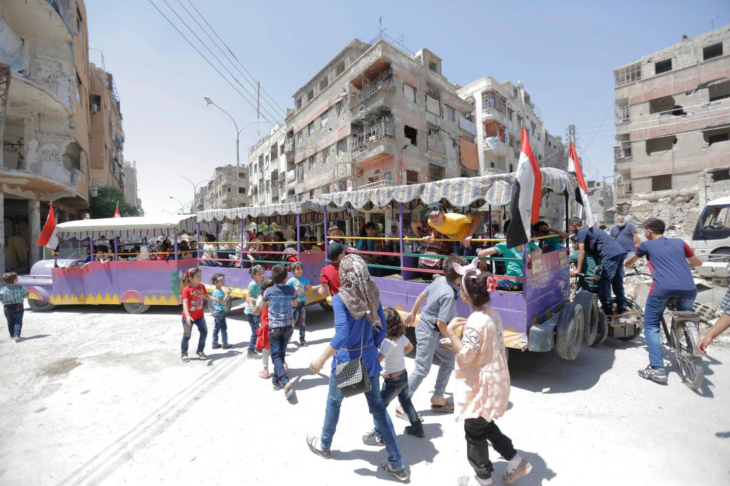 epaselect epa06810011 Adults and children ride a fun train amid destroyed houses in Douma City, eastern Ghouta region, Syria, 15 June 2018. The Islamic Army group held the city for several years before being liberated by the Syrian army two months ago. Muslims around the world are preparing to celebrate Eid al-Fitr, the three day festival marking the end of the Muslim holy month of Ramadan, it will be observed on 15th or 16th of June depending on the lunar calendar. Eid al-Fitr is one of the two major holidays in Islam.  EPA/YOUSSEF BADAWI