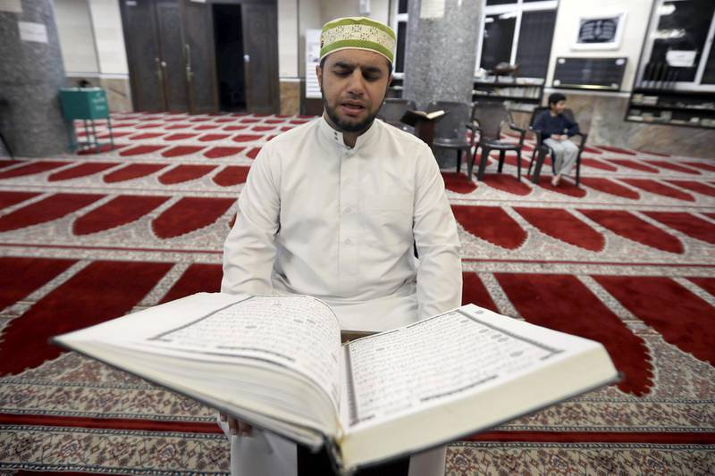 A Jordanian Imam Ahmad Al-Harasis, reads the Koran at empty Abdullah Ben Sallam mosque during the holy fasting month of Ramadan as prayers by worshippers in the holy places are suspended due to concerns about the spread of the coronavirus disease (COVID-19), in Amman, Jordan April 26, 2020. Picture taken April 26, 2020. REUTERS/Muhammad Hamed
