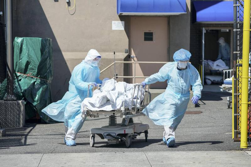 """Bodies are moved to a refrigeration truck serving as a temporary morgue at Wyckoff Hospital in the Borough of Brooklyn on April 6, 2020 in New York. - New York Governor Andrew Cuomo on Monday extended a shutdown in the epicenter of America's deadly coronavirus pandemic until near the end of the month. Cuomo said the COVID-19 death rate in New York was """"effectively flat"""" for the past two days but announced that schools and non-essential businesses must stay shut until April 29. (Photo by Bryan R. Smith / AFP)"""