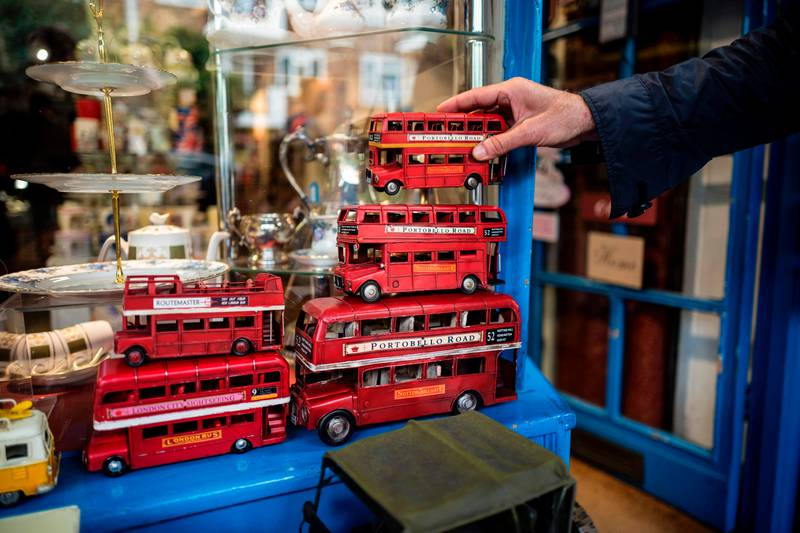 A customer looks a model of a red London Bus outside a shop on the Portobello Road Market in the Notting Hill district of west London, on August 8, 2017. Last week, The Bank of England cut its UK growth forecasts with governor Mark Carney warning that high inflation triggered by a Brexit-fuelled slump in the pound had hurt consumer spending. / AFP PHOTO / Tolga Akmen