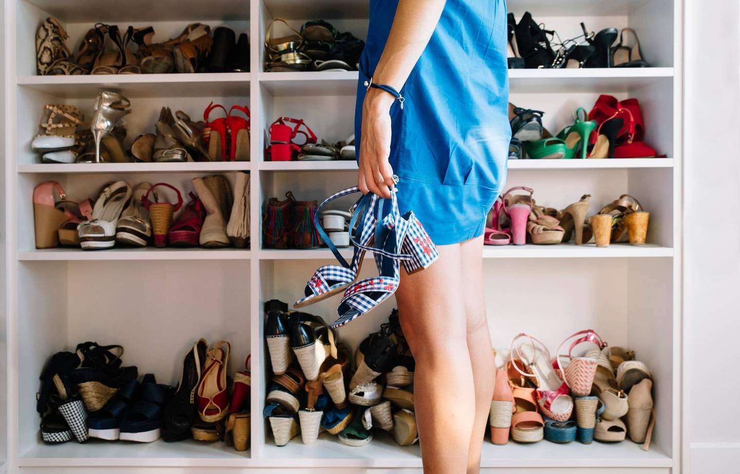 Woman with the shoes in the hand and Woman's shoes in the rack. Getty Images