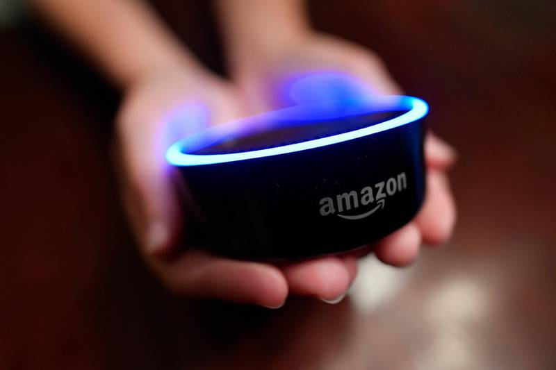 FILE - In this Aug. 16, 2018, file photo a child holds his Amazon Echo Dot in Kennesaw, Ga. Amazon met with skepticism from some privacy advocates and members of Congress last year when it introduced its first kid-oriented voice assistant , along with brightly colored models of its Echo Dot speaker designed for children. (AP Photo/Mike Stewart, File)