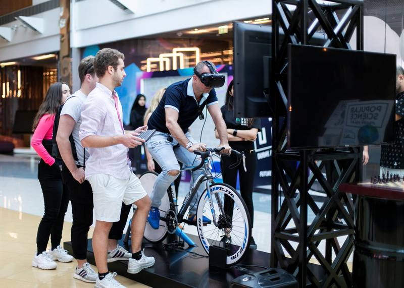 """DUBAI, UNITED ARAB EMIRATES. 3 NOVEMBER 2019. VR excercise bike.Dubai Future Foundation (DFF) launched Dubai Future Week which offers a schedule of community events and interactive workshops at AREA 2071 in Emirates Tower, as part of efforts to offer a global futuristic experience that promotes technological knowledge and applications.Under the theme: """"Imagining, Designing and Executing the Future"""", participants will have the opportunity to preview international films that envision the future, play Human Experience 2.0, an awareness game that introduces futuristic technologies, marvel at the Future Exhibition of images, shopping and the future of food, and engage in Future Dialogues which will explore various sectors such as education, workforce, economics and transportation.(Photo: Reem Mohammed/The National)Reporter:Section:"""