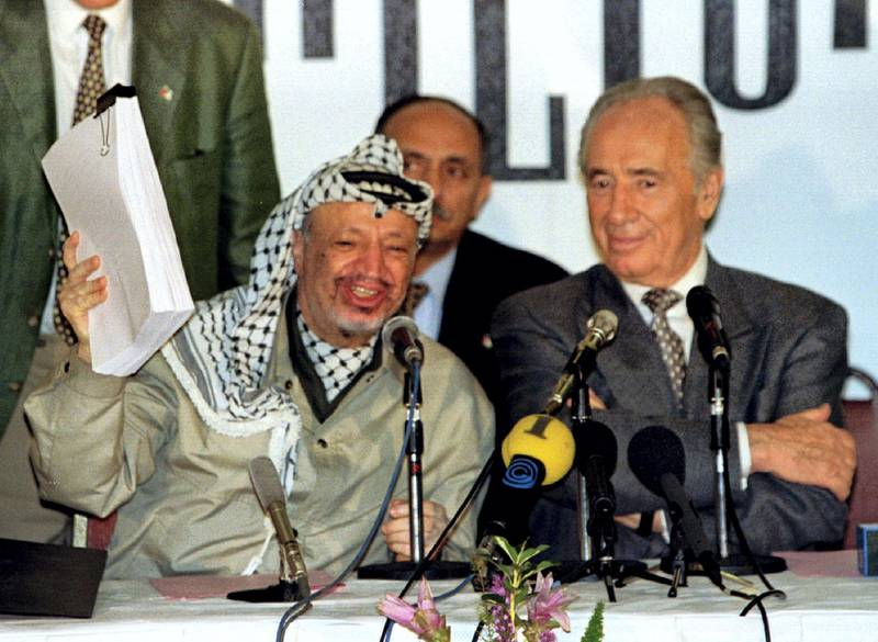 PLO chairman Yasser Arafat holds the second phase of the Oslo peace accords after the initialling of the document, September 24, as Israeli Foreign Minister Shimon Peres looks on. Israel and the PLO will officially sign the agreement in Washington later this week. **POOR QUALITY DOCUMENT
