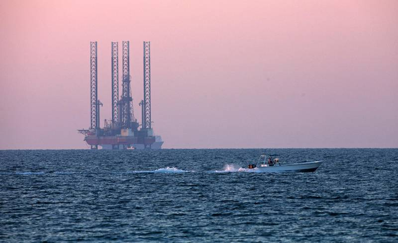 Sharjah, November 29, 2010 - A boater speeds along the water during sunset with an oil derrick in the background near the Beach Hotel in the Al Khan neighborhood in Sharjah, November 29, 2010. (Jeff Topping/The National)