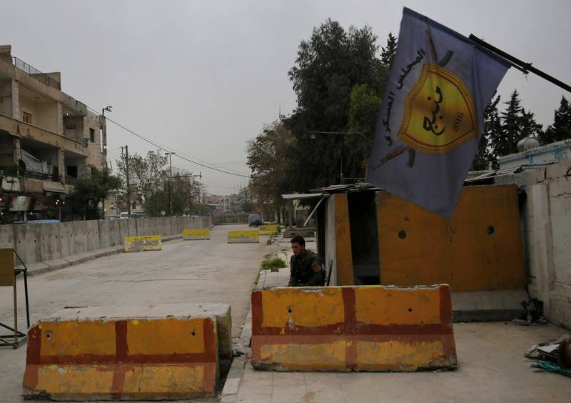 In this photo taken on Wednesday, March 28, 2018, a Syrian fighter from the Kurdish police, guards the entrance of the Manbij Military Council the Kurdish led militia group that defending Manbij, north Syria. Manbij, a mixed Arab and Kurdish town of nearly 400,000, was liberated from Islamic State militants in 2016 by the YPG fighters with backing from U.S-led coalition airstrikes. With Turkey's threats, the town has become the axle for U.S. policy in Syria, threatening its prestige and military deployment in eastern Syria. (AP Photo/Hussein Malla)
