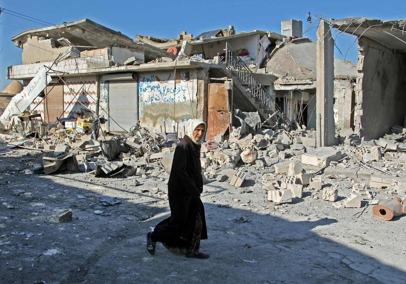EDITORS NOTE: Graphic content / A Syrian woman walks past destruction at the site of a reported government bombardment in the village of Maasaran on the outskirts of Maaret al-Numan in Syria's northwestern Idlib province on December 17, 2019.  / AFP / Abdulaziz KETAZ