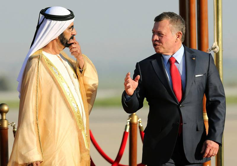 Jordan's King Abdullah II (R) talks with the Prime Minister of the United Arab Emirates (UAE) and ruler of Dubai Sheikh Mohammed bin Rashid al-Maktoum during a welcome ceremony at the Queen Alia International Airport in Amman on March 28, 2017 ahead of talks on the eve of the Arab League summit. (Photo by Khalil MAZRAAWI / AFP)