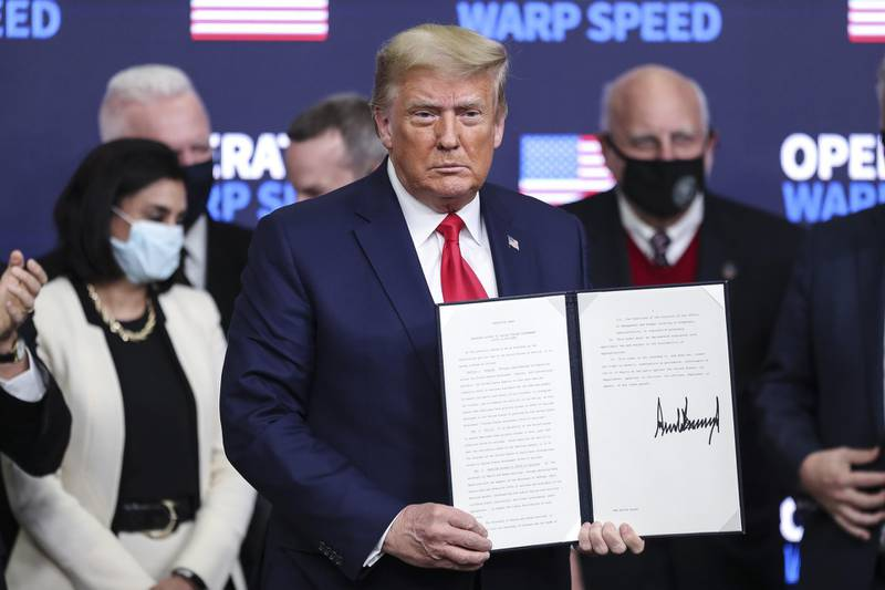 U.S. President Donald Trump holds a signed executive order during an Operation Warp Speed vaccine summit at the White House in Washington, D.C., U.S., on Tuesday, Dec. 8, 2020. Trumpcelebrated the development of coronavirus vaccines at a White House summit on Tuesday and vowed to use executive powers if necessary to acquire sufficient doses, as the number of U.S. cases surpassed 15 million. Photographer: Oliver Contreras/SIPA USA/Bloomberg