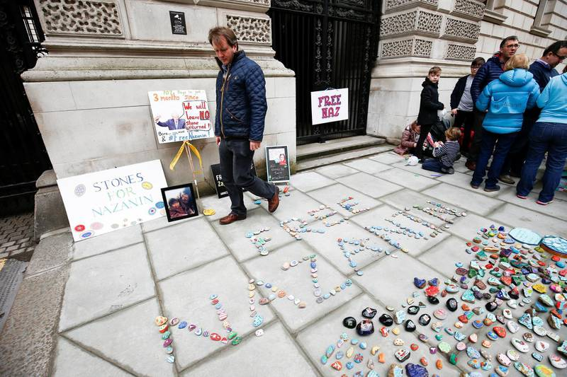 Richard Ratcliffe views stones and placards with messages placed on the pavement outside the Foreign and Commonwealth Office during a demonstration to demand the release of his wife Nazanin Zaghari-Ratcliffe, who is imprisoned in Iran, in London, Britain, March 10, 2018. REUTERS/ Henry Nicholls