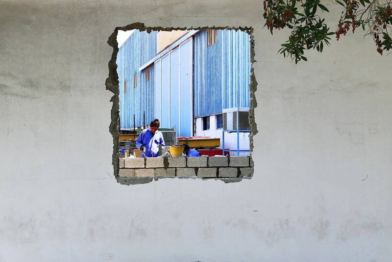 Workers constructing a wall at the Gulf Craft in Umm Al Quwain on April 28,2021. Pawan Singh / The National