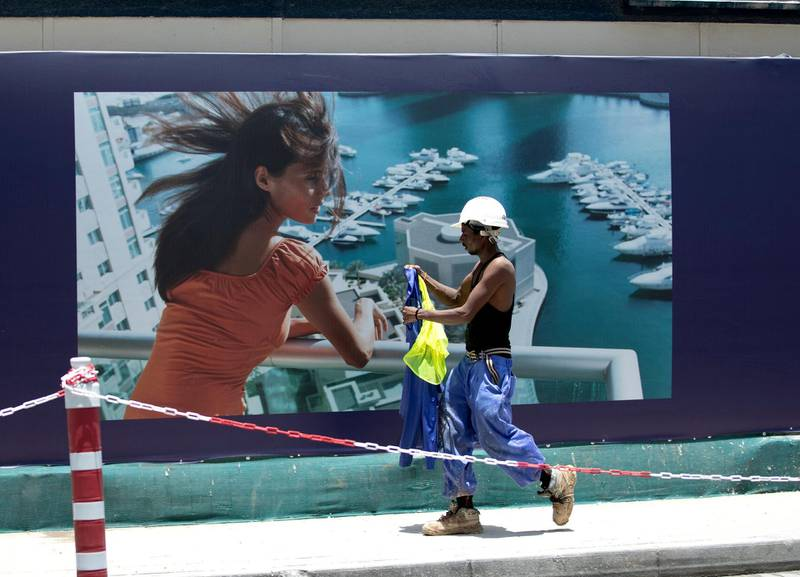 Dubai, U.A.E., June 11,2018.Extreme warm weather at the Dubai Marina area.   A construction worker removes his long sleeved work shirt to cool off.Victor Besa / The NationalSection:  National