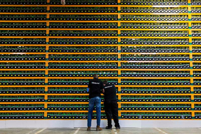 (FILES) In this file photo taken on March 19, 2018 Two technicians inspect bitcon mining at Bitfarms in Saint Hyacinthe, Quebec. Investors in a cryptocurrency exchange who lost access to tens of millions of dollars when the website's Canadian founder died abruptly, are demanding his body be exhumed to rule out any chance that he faked his own death. The case focuses on the sudden death of QuadrigaCX founder Gerald Cotten, who passed away aged 30 from Crohn's disease, an inflammatory bowel condition, in December 2018 while traveling in India, taking all the passwords to the site's funds with him to the grave.  -   / AFP / Lars Hagberg