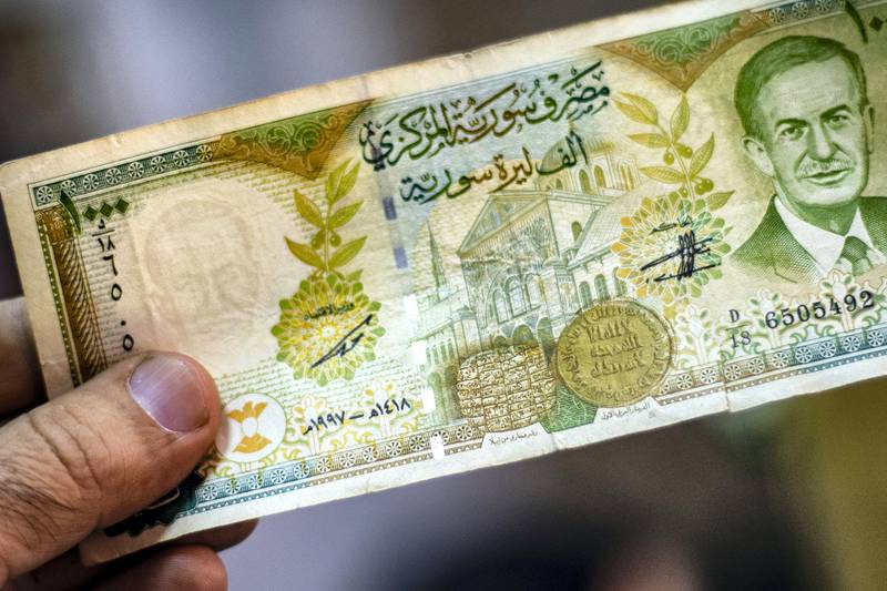 A merchant holds a Syrian pound note, bearing a portrait of late Syrian President Hafez al-Assad, at a market in the Kurdish-majority city of Qamishli in northeast Syria on September 10, 2019. - The declining value of the pound is a sure sign of Syria's ailing economy.  The civil war has battered the country's finances and depleted its foreign reserves.  A flurry of international sanctions on President Bashar al-Assad's regime and associated businessmen since the start of the war in 2011 has compounded the situation. (Photo by Delil SOULEIMAN / AFP)