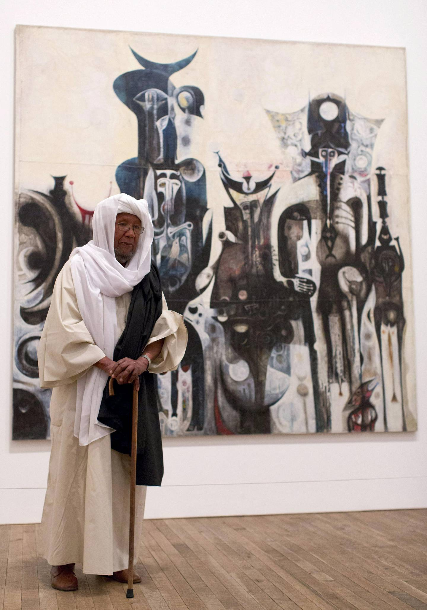 """Sudanese artist Ibrahim El-Salahi poses for a photograph in front of his painting entitled """"Reborn Sounds of Childhood Dreams"""" at the Tate Modern in London on July 1, 2013.  AFP PHOTO/JUSTIN TALLIS - """" RESTRICTED TO EDITORIAL USE, MANDATORY MENTION OF THE ARTIST UPON PUBLICATION, TO ILLUSTRATE THE EVENT AS SPECIFIED IN THE CAPTION """" (Photo by JUSTIN TALLIS / AFP)"""