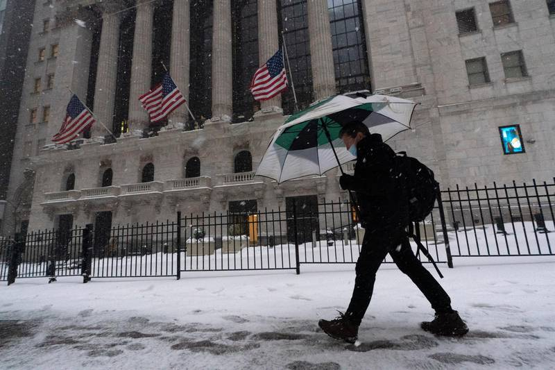 A man walks past the New York Stock Exchange during a snowstorm, Monday, Feb. 1, 2021, in New York. (AP Photo/Mark Lennihan)