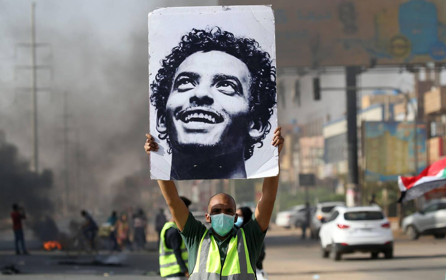 A mask-clad man holds a picture of a Abdulsalam Kisha, a Sudanese protester who was killed in a raid on an anti-government sit-in in 2019, during a protest in the Riyadh district in the east of the capital Khartoum on the anniversary of the raid on June 3, 2020. One year after the 25-year-old Abdulsalam's killing in the dispersal of Sudan's main protest camp, his father Kisha is still holding out hope that the killers be brought to justice as he calls for an international probe. The young protester was killed along with scores others when armed men in military fatigues stormed the sprawling encampment outside Khartoum's army headquarters on June 3 last year. / AFP / ASHRAF SHAZLY