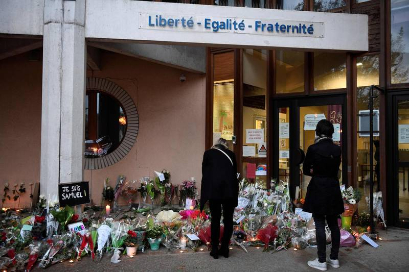 People look at flowers at the entrance of a middle school in Conflans-Sainte-Honorine, 30kms northwest of Paris, on October 17, 2020, after a teacher was decapitated by an attacker who has been shot dead by policemen.  The man suspected of beheading on October 16 ,2020 a French teacher who had shown his students cartoons of the prophet Mohammed was an 18-year-old born in Moscow and originating from Russia's southern region of Chechnya, a judicial source said on October 17. Five more people have been detained over the murder on October 16 ,2020 outside Paris, including the parents of a child at the school where the teacher was working, bringing to nine the total number currently under arrest, said the source, who asked not to be named. The attack happened at around 5 pm (1500 GMT) near a school in Conflans-Sainte-Honorine, a western suburb of the French capital. The man who was decapitated was a history teacher who had recently shown caricatures of the Prophet Mohammed in class. / AFP / Bertrand GUAY