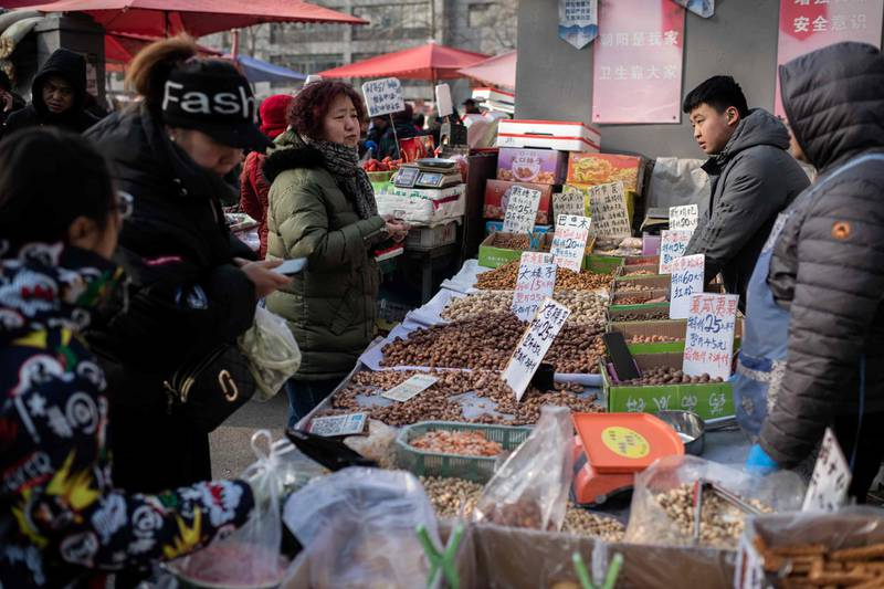 People buy nuts at a market in Beijing on January 17, 2020. China's economy weakened to its slowest pace in three decades in 2019 as weaker domestic demand and trade tensions with the United States took their toll, official data showed on January 17. / AFP / Nicolas ASFOURI