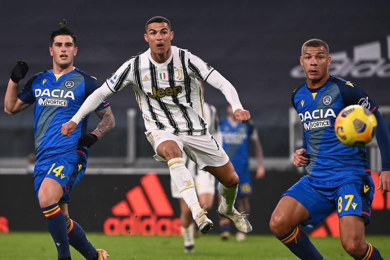 Juventus' Portuguese forward Cristiano Ronaldo (C) shoots to score the opening goal despite Udinese's Italian defender Kevin Bonifazi (L) and Udinese's French defender Sebastian De Maio during the Italian Serie A football match Juventus vs Udinese on January 3, 2021 at the Juventus stadium in Turin. (Photo by Marco BERTORELLO / AFP)
