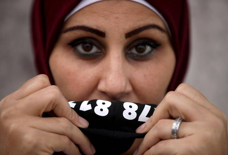 """A Lebanese woman displays a protective mask hiding a hot number distributed by the NGO ABAAD in Beirut on December 8, 2020. ABAAD a resource centre for gender equality distributed masks to women and social workers in Beirut, with the 24/7 helpline of the NGO hidden inside the mask. Many women who are on the frontline, providing safety to their families and their surroundings, are still at risk of sexual harassment, abuse and gender-based violence.  - XGTY / RESTRICTED TO EDITORIAL USE - MANDATORY CREDIT """"AFP PHOTO / ABAAD / PATRICK BAZ- NO MARKETING NO ADVERTISING CAMPAIGNS - DISTRIBUTED AS A SERVICE TO CLIENTS -  / AFP / Abaad / PATRICK BAZ / XGTY / RESTRICTED TO EDITORIAL USE - MANDATORY CREDIT """"AFP PHOTO / ABAAD / PATRICK BAZ- NO MARKETING NO ADVERTISING CAMPAIGNS - DISTRIBUTED AS A SERVICE TO CLIENTS -"""