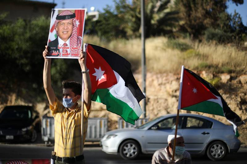 A protester holds a poster of Jordan's King Abdullah as he takes part in a human chain during a sit-in against the annexation of parts of the West Bank by Israel, in Amman, Jordan, June 27, 2020. REUTERS/Muhammad Hamed