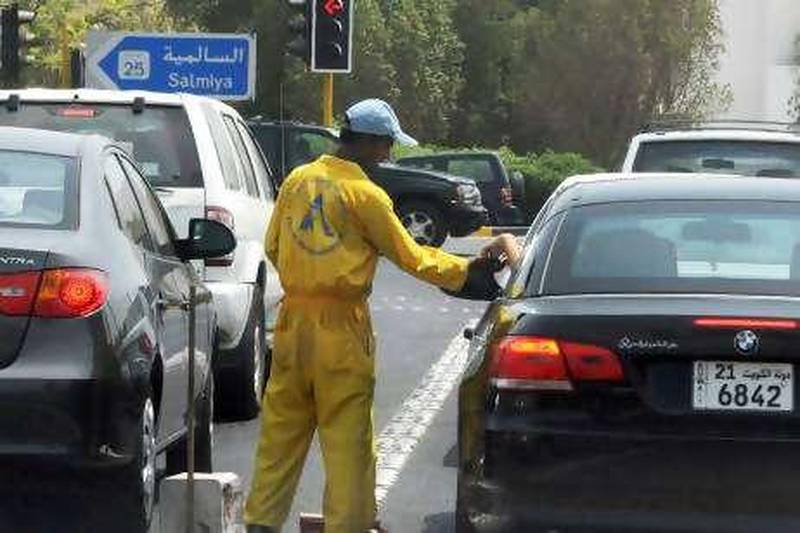 A cleaning worker receives money from a motorist in Salmiya, Kuwait during the last 10 days of Ramadan, August ,2010.(Photo:Gustavo Ferrari/The National)