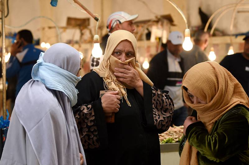 Tunisian women, covering their faces, walk past stalls in a central market in the capital Tunis on April 24, 2020, during the first day of the Muslim holy month of Ramadan, after authorities partially eased the lockdown measures. (Photo by FETHI BELAID / AFP)