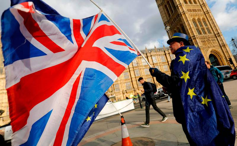 An anti-Brexit demonstrator waves a Union flag as he stands draped in a European Union (EU) flag outside the Houses of Parliament in London on March 28, 2018. With Britain just a year away from leaving the European Union, the transition deal agreed between the two sides is viewed as a key element to absorbing the Brexit shock. British Prime Minister Theresa May kick-started divorce proceedings one year ago, and March 29, 2019, has since been set as the date the UK will leave the bloc. / AFP PHOTO / Tolga AKMEN