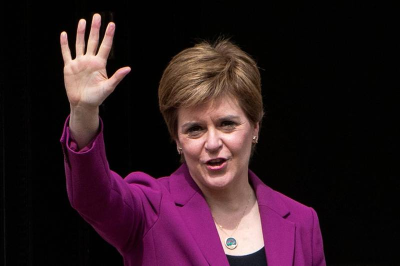 Scotland's First Minister and leader of the Scottish National Party (SNP), Nicola Sturgeon waves on the steps of her official residence Bute House in Edinburgh on May 9, 2021 following the party's landslide victory in the Scottish parliament elections. The Scottish National Party on May 9 said its landslide victory in Edinburgh's devolved parliament was grounds for a fresh independence referendum, despite opposition from London. / AFP / Andy Buchanan