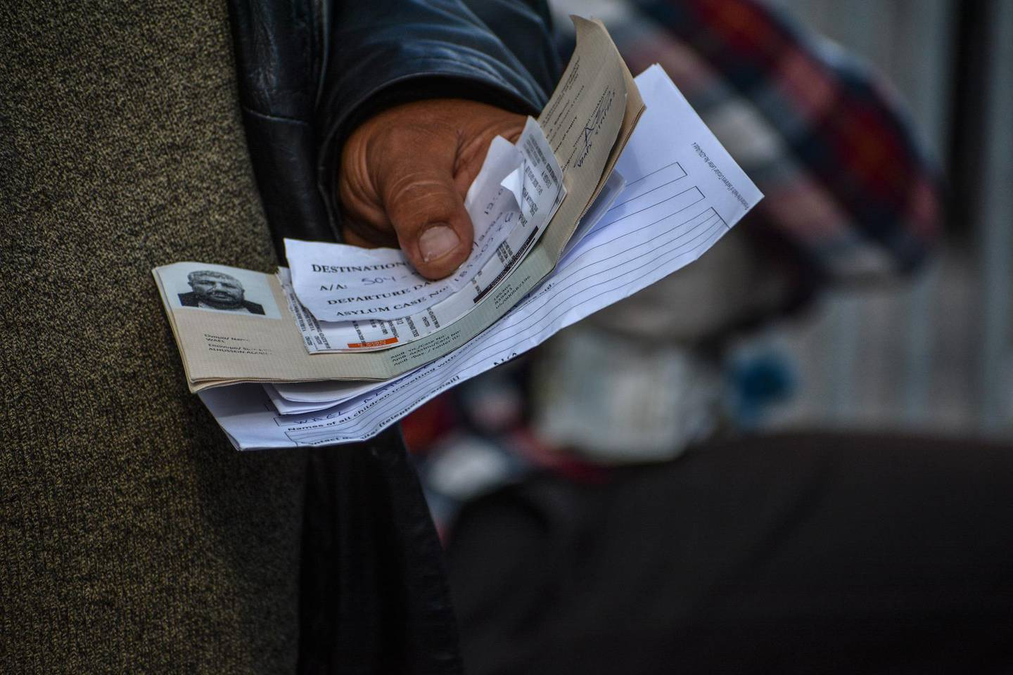 A migrant holds travel documents as he waits to go onboard a ship bound for Piraeus at the port of Mytilene, on the northeastern Aegean island of Lesbos, Greece, on Sunday, May 3, 2020. Greek authorities are moving 400 migrants, mostly families, to the mainland to help ease overcrowded conditions at the camp. The migrants will arrive in the port of Piraeus on two passenger ships Monday morning. (AP Photo/Panagiotis Balaskas)
