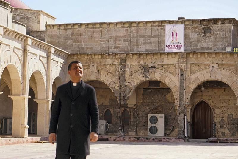 QARAQOSH, IRAQ - 2021/02/25: Father Ammar Yako, the head of the church, walks past a poster of Pope Francis days before his historic visit to Iraq. The town of Qaraqosh, 30 kilometres southeast of the city of Mosul, is preparing to reception Pope Francis by renovating the church that the Pope will visit and by decorating the streets with the Vatican flags and pictures of the Pope on his first and historical visit to Iraq from March 5-8, his historical visit includes a trip to several cities, including the capital Baghdad, the city of Mosul in north and a meeting with the Shiite religious authority Ayatollah Ali Sistani. (Photo by Ismael Adnan/SOPA Images/LightRocket via Getty Images)