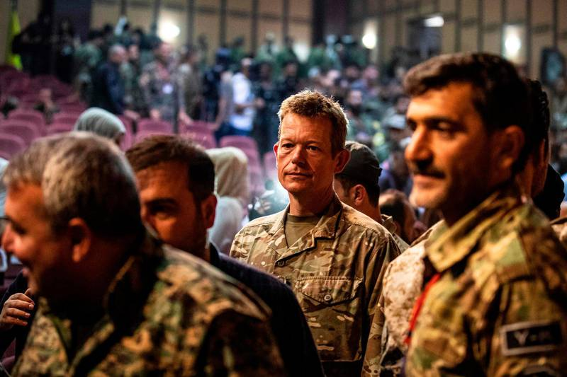 """Brigadier-General Nicholas Pond (C), a representative of the US-led coalition fighting the Islamic State (IS) group, attends a meeting with commanders of the Syrian Democratic Forces (SDF) in the northwestern Syrian city of Hasakah, in the province of the same name, on August 24, 2019. Syria's Kurds said on August 24 that they would support the implementation of a US-Turkey deal to set up a buffer zone in their areas along the Turkish border. The so-called """"safe zone"""" agreed by Washington and Ankara earlier this month aims to create a buffer between the Turkish border and Syrian areas controlled by the Kurdish People's Protection Units (YPG). The YPG have played a key role in the US-backed battle against the Islamic State group in Syria, but Ankara views them as """"terrorists"""". / AFP / Delil SOULEIMAN"""