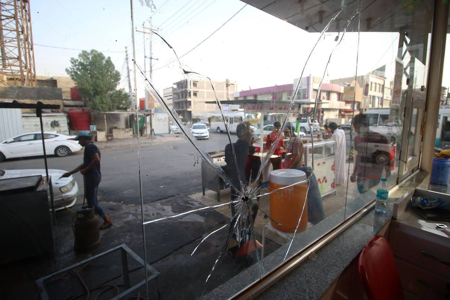 TOPSHOT - Iraqi vendors serving clients are seen through a broken window of a restaurant in a street in the southern Iraqi city of Basra on September 9, 2018. - After several nights of deadly protests, calm returned to the southern Iraqi city of Basra today, even as residents stuck to their demands that Baghdad no longer neglect their region. (Photo by Haidar MOHAMMED ALI / AFP)