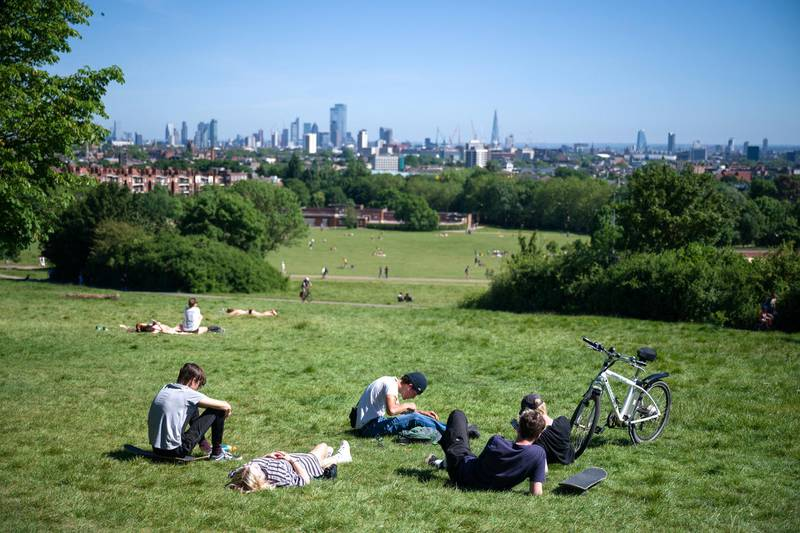 LONDON, UNITED KINGDOM - MAY 29: People sunbathe and socialise on Parliament Hill on May 29, 2020 in London, England. From Monday, groups of up to six people from different households can meet in outdoor spaces, as long as they respect the correct social distancing guidelines. However, as the weather continues to stay at record high temperatures for this time of year, many have chosen to adopt the new guidelines early. The British government continues to ease the coronavirus lockdown by announcing schools will open to reception year pupils plus years one and six from June 1st. Open-air markets and car showrooms can also open from the same date.  (Photo by Leon Neal/Getty Images)