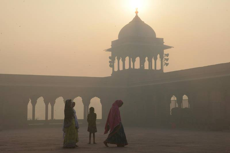 Indian women walk as smog envelops the Jama Masjid Mosque in the old quarters of New Delhi on November 3, 2016.  India's capital, with 18 million residents, has the world's most polluted air, worsening in winter as temperatures drop and farmers burn off fields after the summer harvest. / AFP PHOTO / DOMINIQUE FAGET