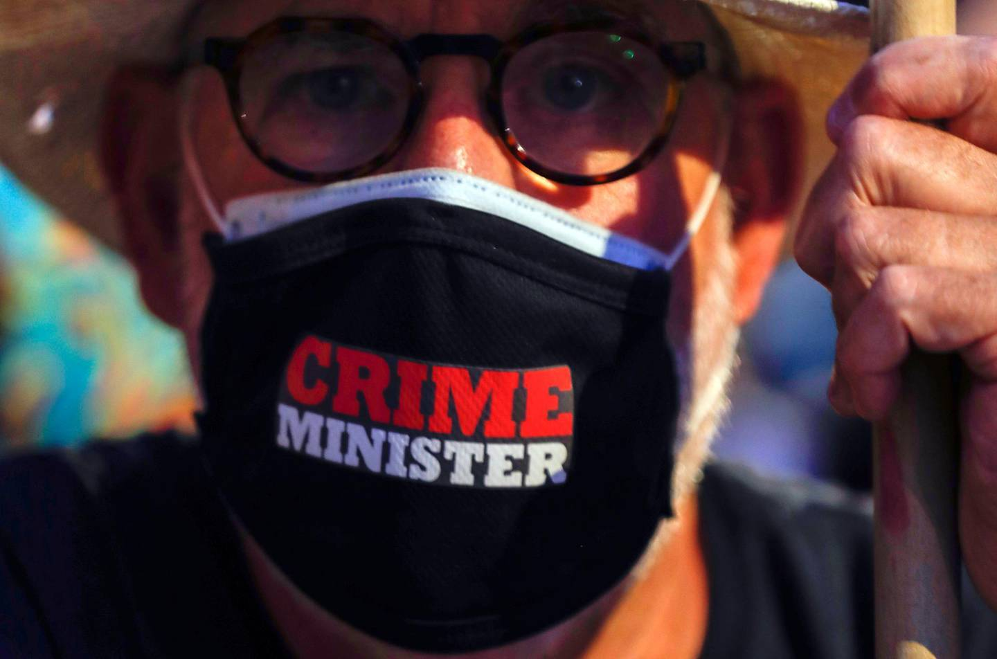 epa08563206 A man with a face mask reading 'Crime Minister' during a protest against Israeli Prime Minister Benjamin Netanyahu outside his residence in Jerusalem, Israel, 23 July 2020. Netanyahu faces an ongoing trial with indictments filed against him by the State Attorney's Office on a charges of fraud, bribery, and breach of trust.  EPA/ATEF SAFADI